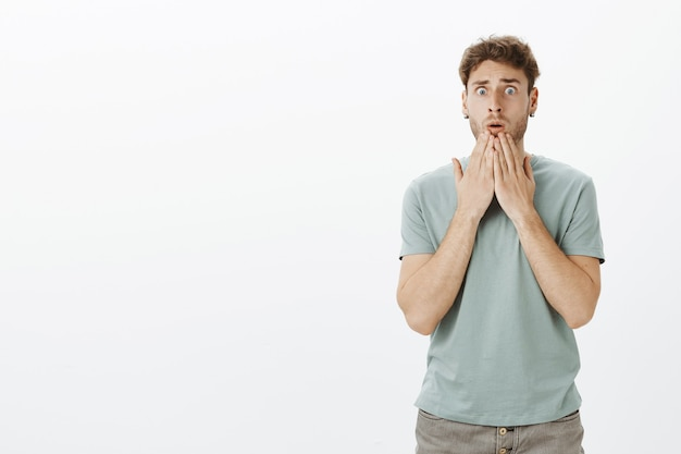 Portrait of worried shocked attractive guy in casual t-shirt, holding palms above mouth and staring nervously, being amazed with terrible accident