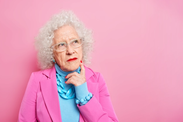 Portrait of wrinkled thoughtful grey haired senior lady concentrated aside recalls her youth dressed in fashionable clothes has bright makeup dresses for special occasion