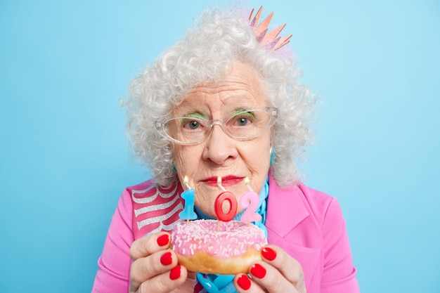 Portrait of wrinkled woman with curly grey hair holds glazed doughnut with number candles celebrates 102nd birthday has red nails wears makeup looks directly,