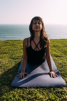 Portrait of a yoga teacher stretching her body outside the home. copy space