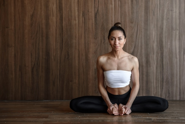 Portrait of a yoga woman sitting in a butterfly pose in yoga and looking at the camera