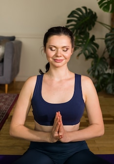 Portrait of a yoga woman with folded hands and closed eyes in a room