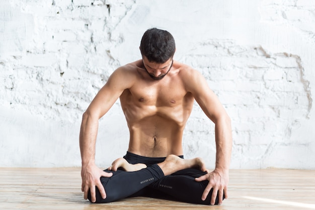 Portrait of yogi men doing abs exercise, he breath and practicing upward abdominal lock