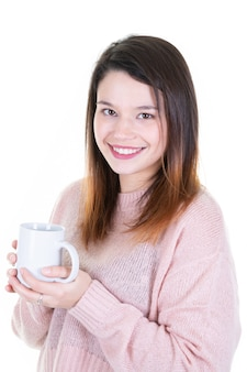 Portrait of a young adorable brunette woman enjoying her warm cozy drink in big blank white mug
