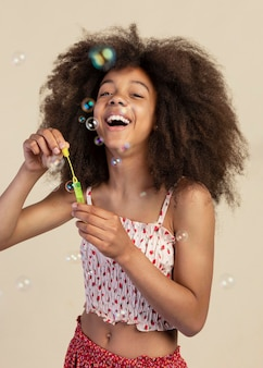 Portrait of young adorable girl posing while playing with soap bubbles