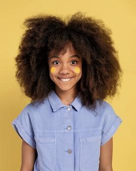 Ritratto di giovane ragazza adorabile in posa con adesivi emoji sul viso