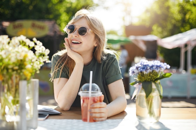 Portrait of young adorable woman drinking lemonade in park surronded by flowes