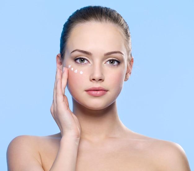 Ritratto di giovane ragazza adulta che applica la crema sulla sua pelle intorno agli occhi sull'azzurro