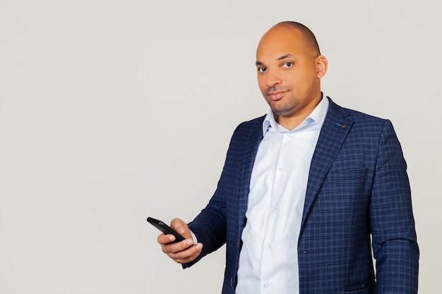 肖像画の若いアフリカ系アメリカ人ビジネスマンの男は、スマートな顔に自信を持って表情でスマートフォンを使用し、真剣に考えてメッセージを読みます。