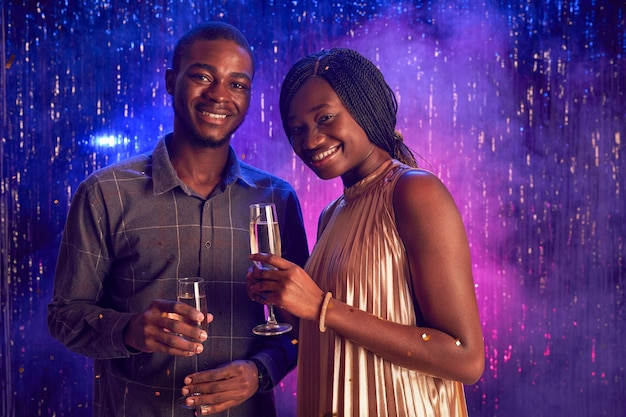 Portrait of young african-american couple holding champagne glass and smiling at camera while enjoying party in nightclub, copy space