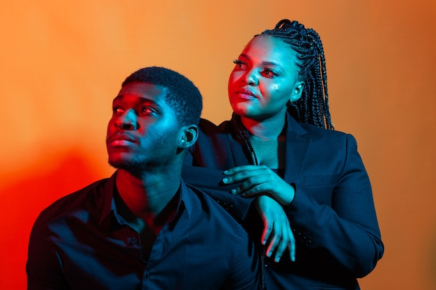 Portrait of young african american couple in love posing dressed in classic clothes. neon