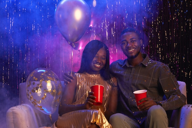 Portrait of young african-american couple smiling at camera while sitting on couch against sparkling background and enjoying party, copy space