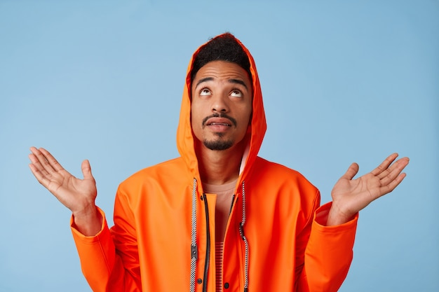 Portrait of young african american dark skinned guy in orange rain coat, hopes for good luck looking up raising, spreading his arms to the side, stands isolated with copy space.