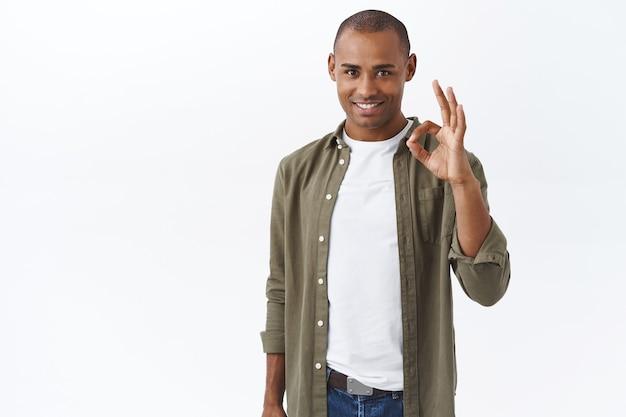 Ritratto di giovane uomo determinato afroamericano, garantisce una buona qualità, assicura al cliente di investire in azienda