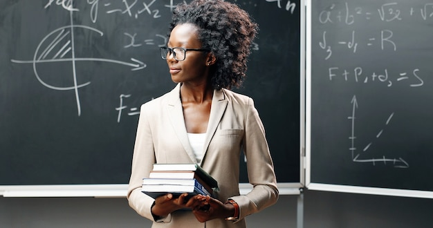 Portrait of young african american female teacher in glasses looking at camera in classrom and holding textbooks. blackboard with formulas on background. schooling concept. books in hands of woman.