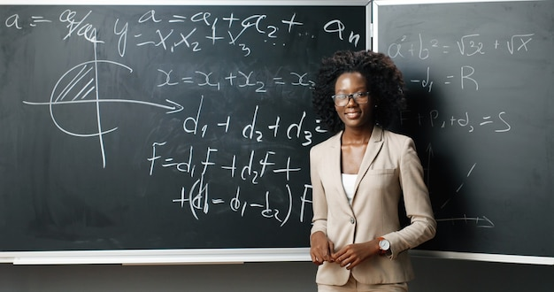 Portrait of young african american female teacher in glasses standing at board, writing with chalk math or physics laws and formulas and smiling to camera at class. education concept.