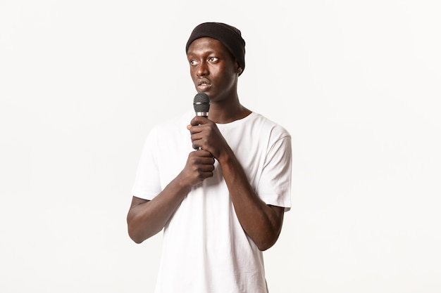 Portrait of young african-american guy in beanie, singing karaoke, looking left and holding microphone