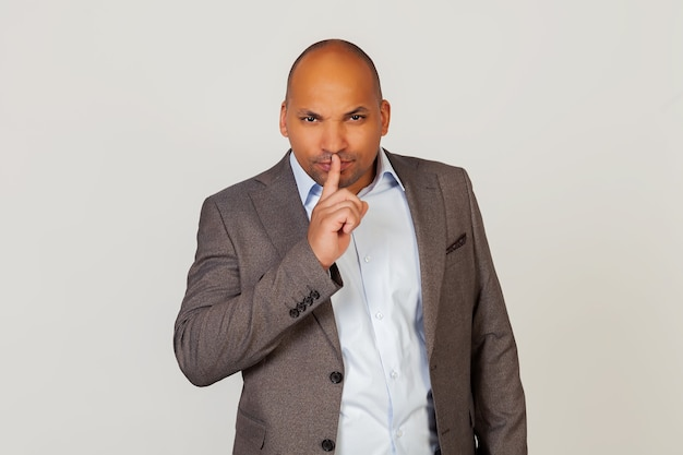 Portrait of a young african american guy businessman holding a finger on his lips, shows to close his mouth and stop making noise at the wrong moment.