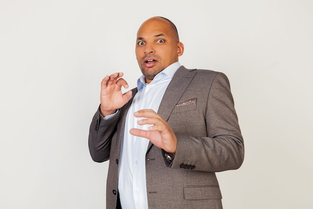 Portrait of a young african american guy businessman screaming with a frightened expression on his face. a frightened man defends himself with his hands. negative emotion