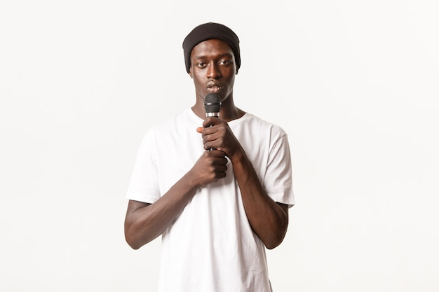 Portrait of young african-american guy performing song, holding microphone and singing karaoke
