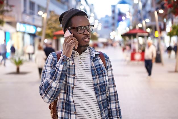 Ritratto di giovane maschio afroamericano che indossa abbigliamento e accessori alla moda che parla sullo smartphone sulla via di casa