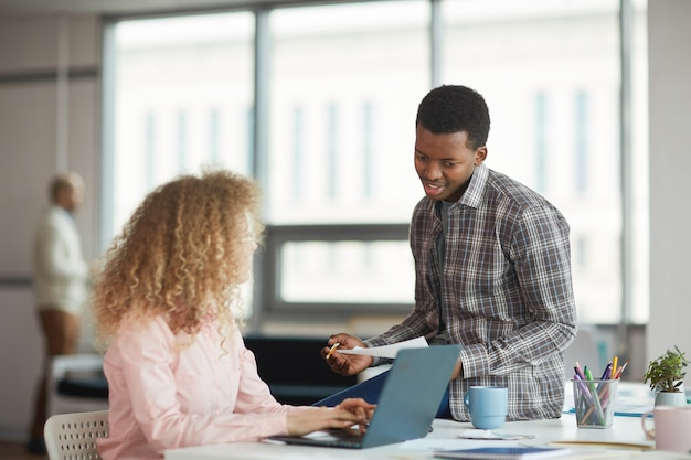 Portrait of young african-american man discussing business project with female colleague in modern office, copy space