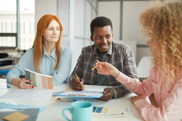 Portrait of young african-american man discussing creative project during meeting with team in modern office, copy space