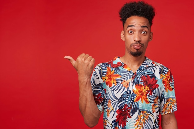Portrait of young african american man in hawaiian shirt, looks amazed and happy, stands over red background, points to the left at copyspace.