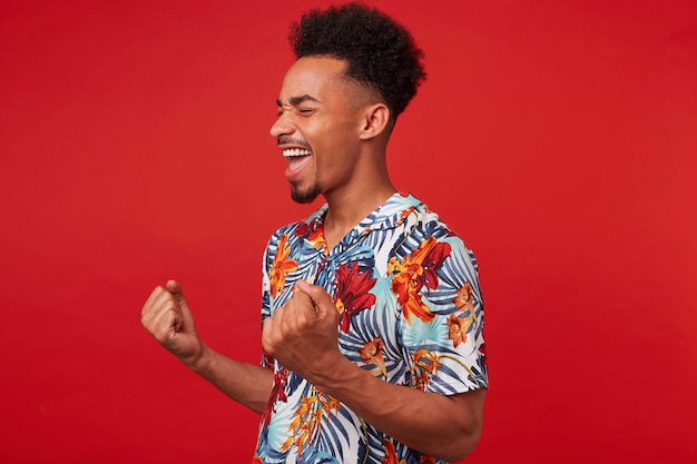 Portrait of young african american man in hawaiian shirt, looks happy and joyful, stands over red background and clenches fists and rejoices victory.