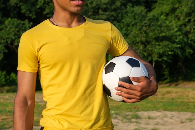 Portrait of young african-american man holding soccer ball while standing outdoors in park in summer