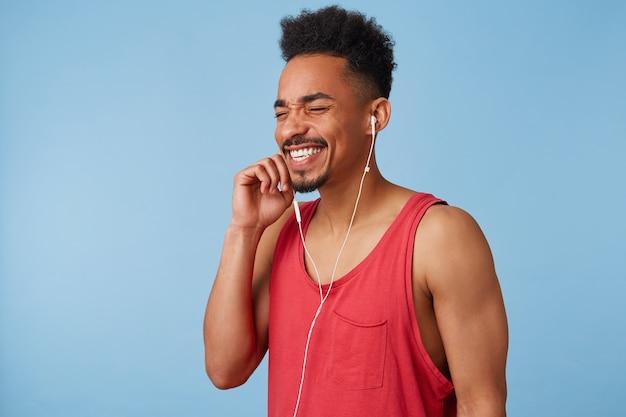 Ritratto di giovane uomo afroamericano amanti della musica si sente bene e molto felice, chiudi gli occhi, gode della sua lista di brani preferiti, canta e balla stand.