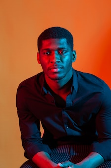 Portrait of a young african american man on orange neon light.