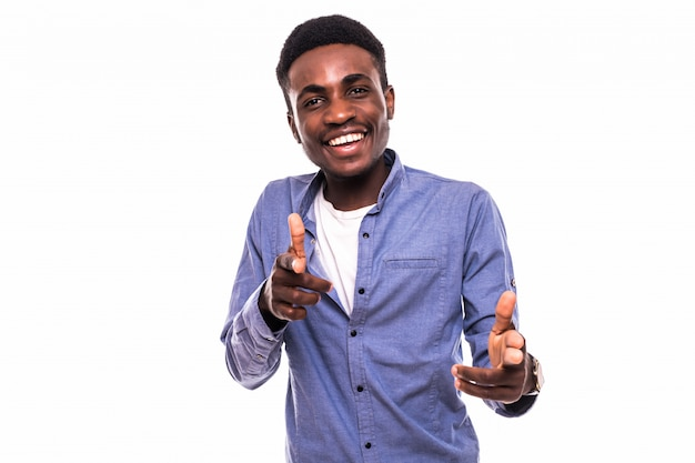Ritratto di giovane uomo afro-americano che punta su di te e sorridente, sul muro bianco