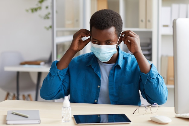 Portrait of young african-american man putting on face mask while working at desk in post pandemic office