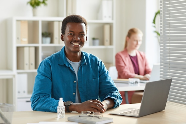 Portrait of young african-american man smiling working at desk in office with colleagues