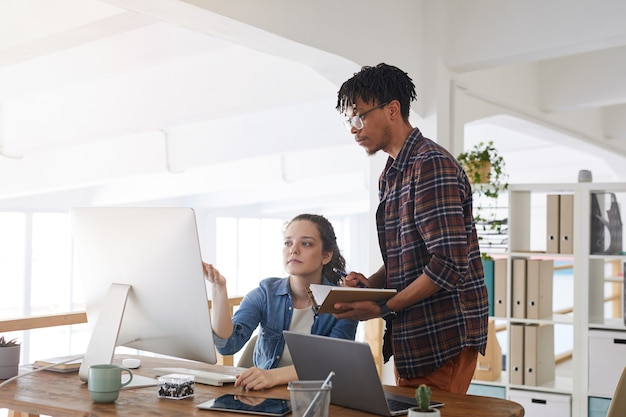 Portrait of young african-american man talking to female colleague while standing by computers in modern office, it developers concept, copy space
