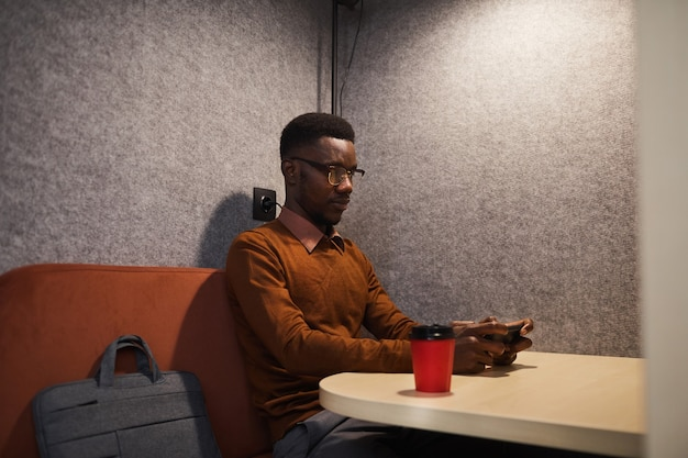 Portrait of young african-american man using smartphone while sitting alone in cafe booth, copy space