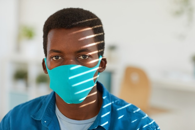 Portrait of young african-american man wearing face mask posing at sunlit workplace in post pandemic office