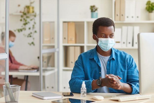 Portrait of young african-american man wearing face mask and sanitizing hands while working in cubicle at post pandemic office