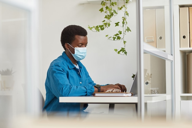 Portrait of young african-american man wearing face mask while working in cubicle at post pandemic office