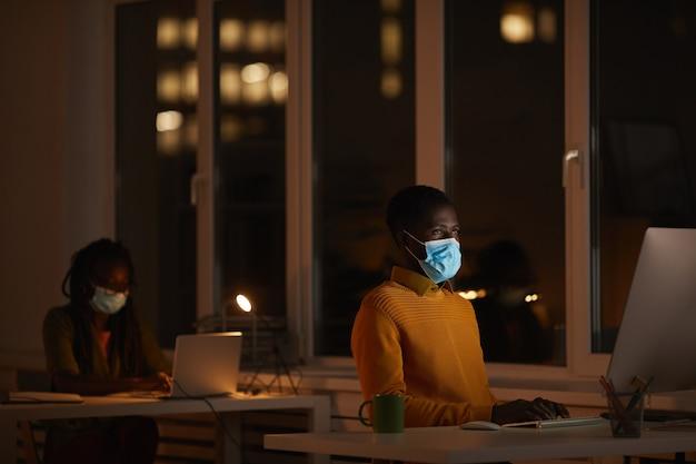 Portrait of young african-american man wearing mask in office while using computer lit by screen in dark, copy space
