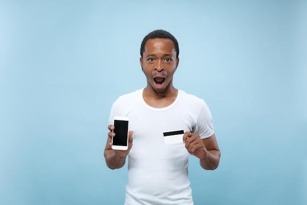 Ritratto di giovane uomo afro-americano in camicia bianca che tiene una carta e smartphone.