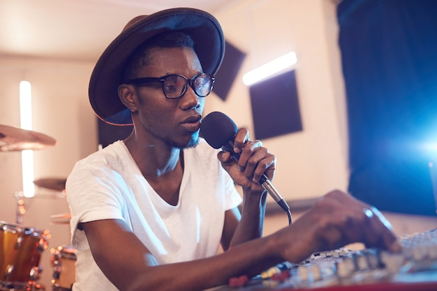 Portrait of young african-american man writing music in recording studio