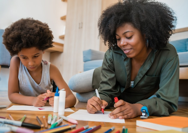 Portrait of young african american mother and son drawing with colored pencils on warm floor at home