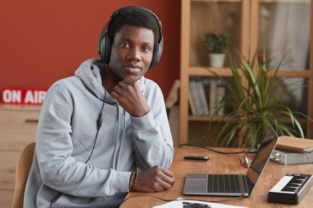 Portrait of young african-american musician looking at camera and using laptop while making music at home, copy space