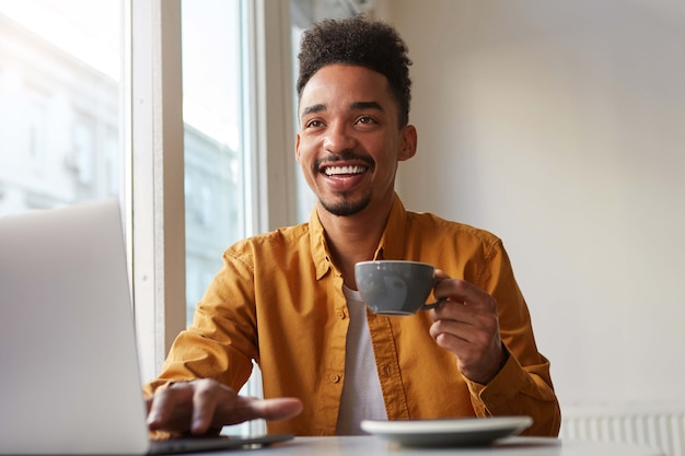 Portrait of young african american positive guy, sits in a cafe and works at a laptop, broadly smiling and looks away, enjoying aromatic coffee.