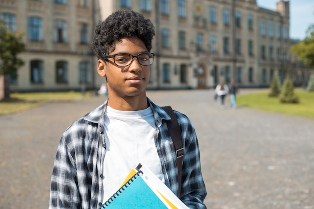 Portrait of a young african american student black man the background of college.