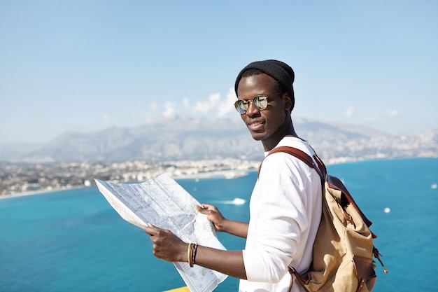 Portrait of young african american traveler looking with paper map in his hands, wearing sunglasses and hat, standing on viewing platform, admiring european city and beautiful seascape