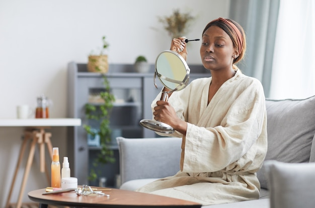 Portrait of young african-american woman doing makeup at home in morning, copy space