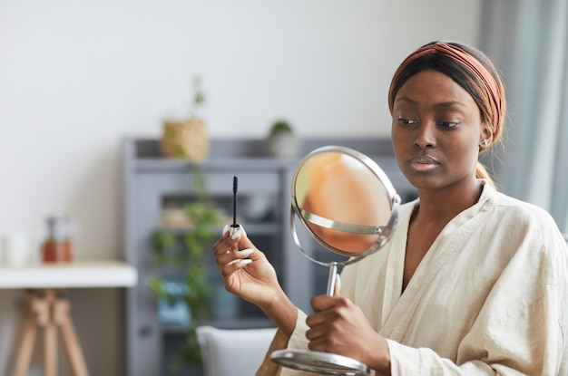 Portrait of young african-american woman doing makeup at home in morning and looking at mirror , copy space